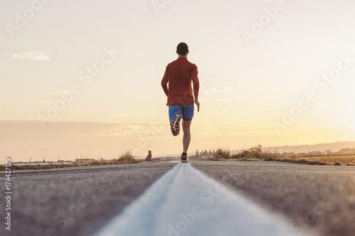 Uomo che corre su strada asfaltata