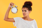 Displeased african woman holding alarm clock and looking on them - 176433591