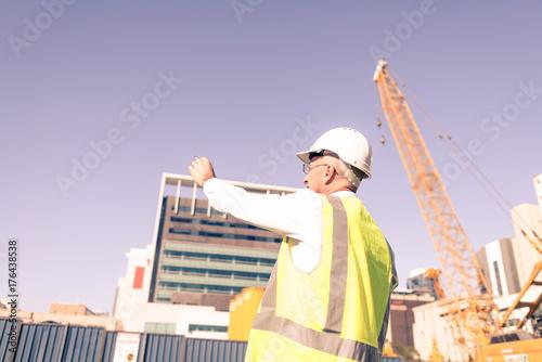 Senior foreman in glasses doing his job at building area on sunn