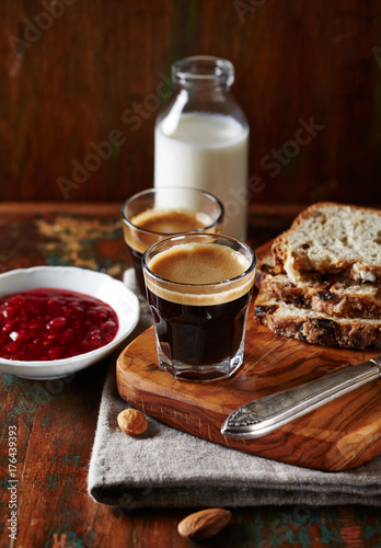Glasses of espresso and rustic yeast cake with dried fruits and nuts