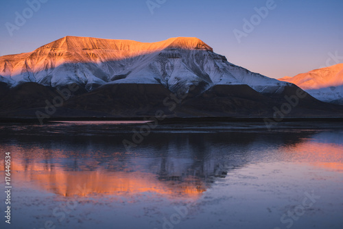 Fridge magnet Landscape of a nature of a  pink sunset  in the reflection ocean mountains of Spitsbergen Svalbard near the Norwegian city Longyearbyen