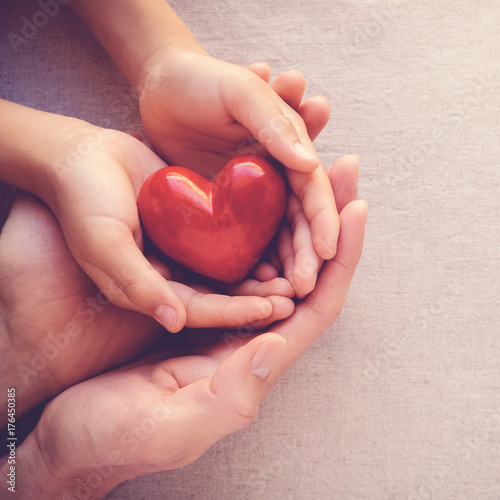 adult and child hands holiding red heart, health care love and family concept
