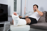 Smiling Young Injured Man Talking On Mobile Phone - 176466924