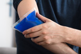 Person Applying Ice Gel Pack On An Injured Elbow - 176468302