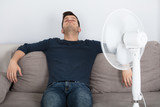 Man Sitting On Couch Cooling Off With Fan - 176468347
