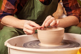 Close-up A woman potter in a plaid shirt and green apron beautifully sculpts a deep bowl of brown clay and cuts off excess clay on a potter's wheel in a beautiful workshop - 176469114