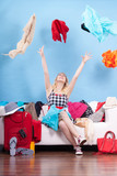 Woman throwing up clothes, clothing flying everywhere - 176469718