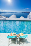 Couple  by the swimming pool  in Santorini Greece - 176475143