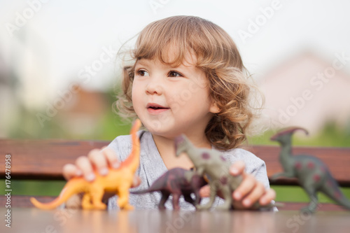 Toddler kid playing with a toy dinosaurs outdoors. Poster