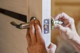 man repairing the doorknob. closeup of worker's hands installing new door locker - 176481138