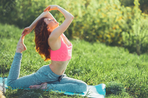 Fototapeta Sporty young woman doing yoga practice - concept of healthy life
