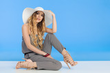 Beautiful Young Woman In White Sun Hat Is Sitting On Floor - 176501352
