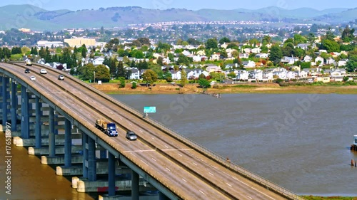 Poster Truck with hauling cargo crossing over Napa river bridge with light traffic near Vallejo, California with city in the background