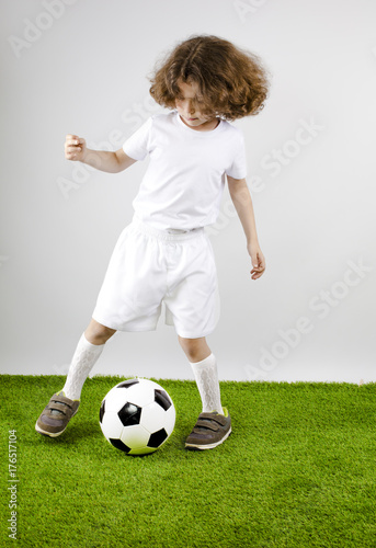 Aluminium Voetbal Young football player playing soccer on the grass. Gray background.
