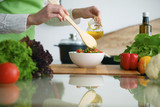 Closeup of human hands cooking vegetables salad in kitchen on the glass  table with reflection - 176519342