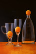 Still life with orange balls and glass objects
