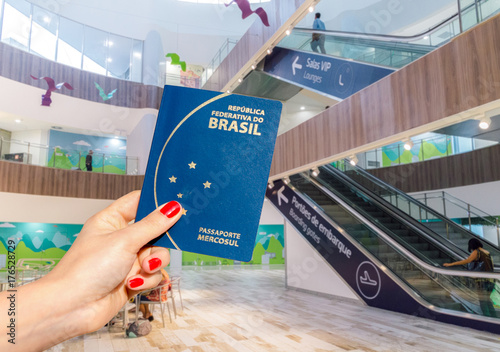 Hand holding a Brazilian passport inside a brightly lit airport terminal Poster
