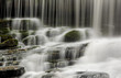 Closeup of waterfall cascading over rocks and moss