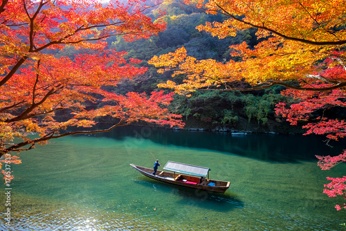 Papiers peints Kyoto Boatman punting the boat for tourists to enjoy the autumn view along the bank of Hozu river in Arashiyama Kyoto, Japan.