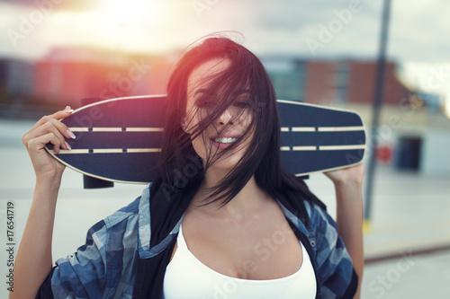 Aluminium Skateboard Young woman holding skateboard in sunset portrait