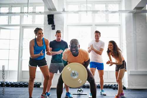 Man weightlifting with friends encouraging him in the background