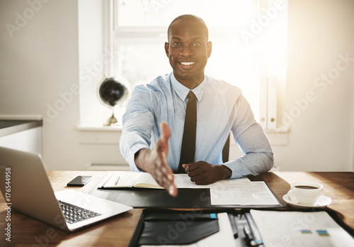 Fridge magnet Smiling young executive sitting at his desk extending a handshak