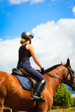 Jockey girl doing horse riding on countryside meadow - 176551326