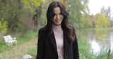 Pretty woman in black jacket and polo-neck shirt standing near pond, enjoying weather and looking at camera. - 176558118