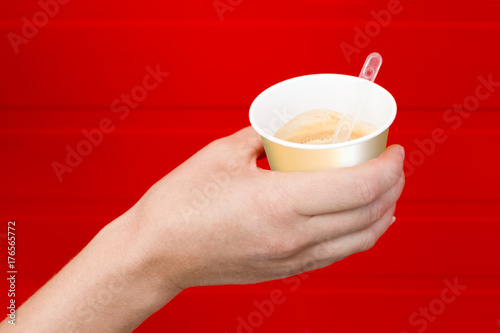 Papiers peints Cafe A glass with a drink in his hand. Horizontally. A hand holding a disposable glass with a drink on a bright red background.