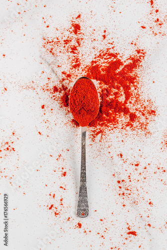 Fotobehang Hot chili peppers Dried ground chili pepper in spoon on white marble background top view copy space