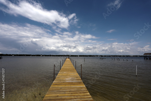 Aluminium Pier dock into soundside water with sky clouds