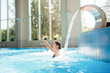 Quadro Young happy woman enjoying warm waterfall in spa jacuzzi