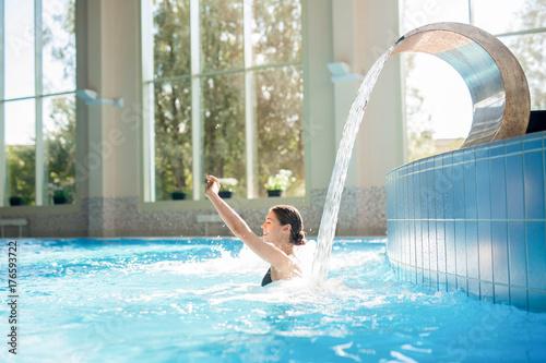 Young happy woman enjoying warm waterfall in spa jacuzzi