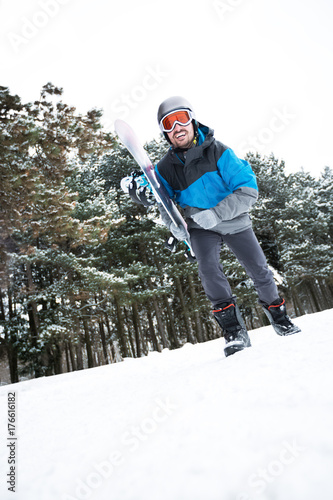 Young man going with snowboard on top of the high mountain to ski slopes Poster