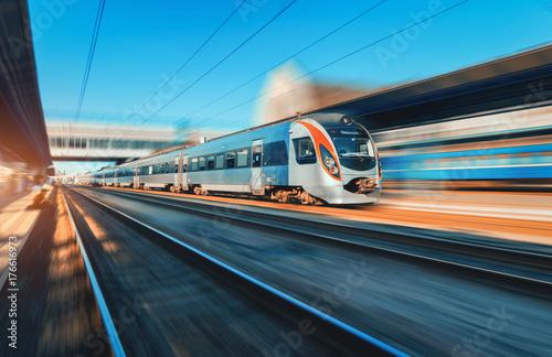 Wysoki prędkość pociąg w ruchu przy stacją kolejową przy zmierzchem w Europa. Nowoczesny pociąg intercity na peronie kolejowym z efektem rozmycia w ruchu. Przemysłowa scena z poruszającym pociągiem pasażerskim na linii kolejowej