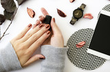 Female hands with nail polish on white background with mobile phone, watch and autumn petals. - 176620368