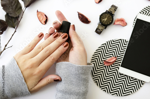 Female hands with nail polish on white background with mobile phone, watch and autumn petals.
