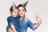 Beautiful mother with daughter dressed equally photographed on the phone in holiday caps on a white background - 176621717