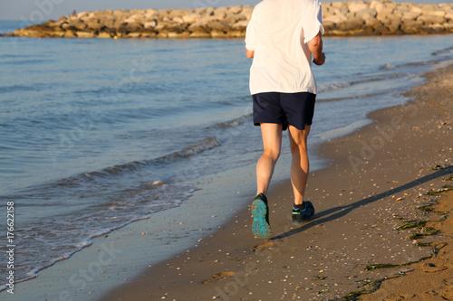 Fotobehang Hardlopen senior person jogging on the beach by the sea