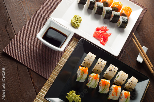 Fotobehang Sushi bar Sushi rolls on a black and white plate, on a wooden mat with chopsticks and soy sauce