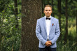 Young handsome groom in blue jacket is posing on a wedding walk in the forest. Wedding day.