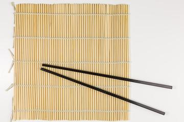 bamboo sushi mat with black chopsticks