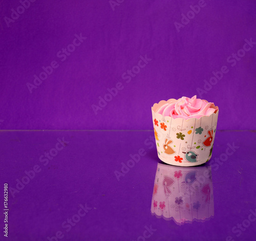 One cup cake on the purple background and reflect on the floor. cupcake is a small cake baked in a cup-shaped container. - 176632980