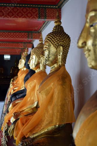 budas dorados cubiertos con velos naranjas en Tailandia Poster