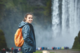 Girl in waterproof clothing stands on background of Skogafoss waterfall in Iceland.