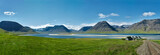 Travel to Iceland. beautiful sunrise over the ocean and fjord in Iceland. Icelandic landscape with mountains, blue sky and green grass on the foreground. View of the road to houses in the north-west - 176642527