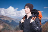 Portrait of young man with backpack on the background of a mountain landscape and a blue sky with white clouds. Mountain Hiking, climbing.