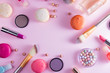 Make up products and macaroons frame on pink background