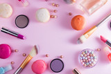 Make up products and macaroons frame on pink background - 176646569