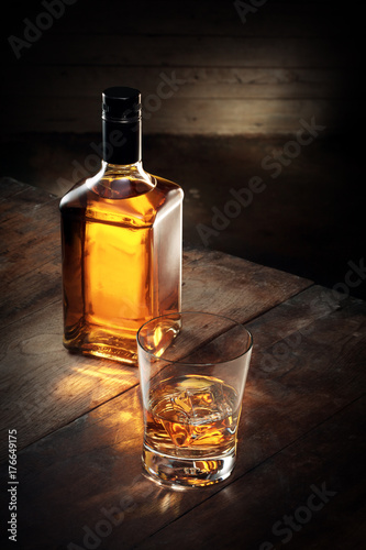 close up view of glass of  whiskey and a bottle aside on color background